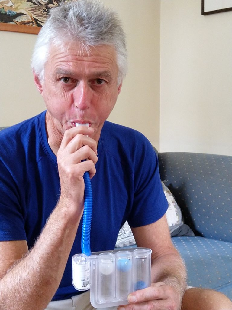 Mish blowing into plastic device to exercise lungs